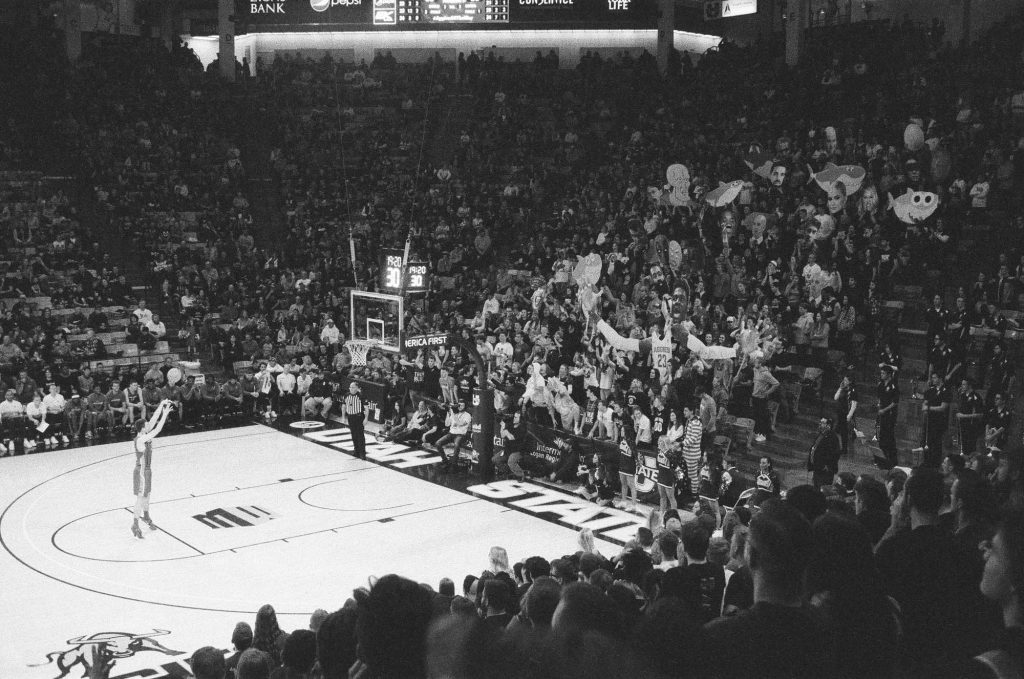 Utah State University's student section distracts an opposing player's free throw with signs and loud noises. Indoor photo at the Spectrum Basketball Stadium with a Rollei 35 camera.
