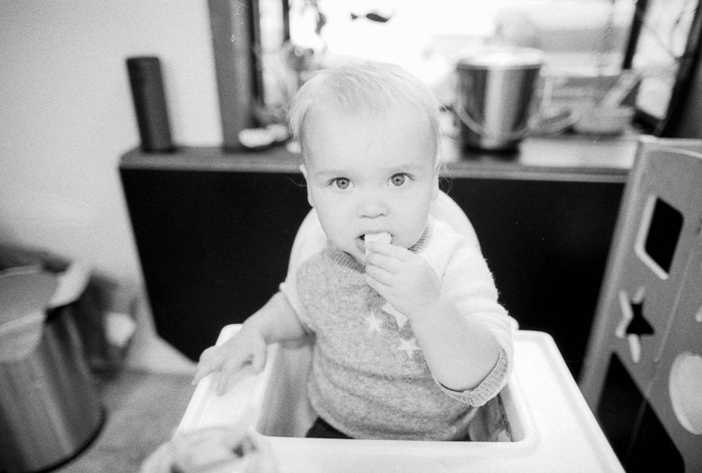Child eats food This shows the way that it renders skin tones with a bounce flash. I think that when overexposed K400 creates a really appealing contrast that makes eyes really pop. Canon EOS 3, Canon 24mm f1.4 lens, bounce flash off ceiling