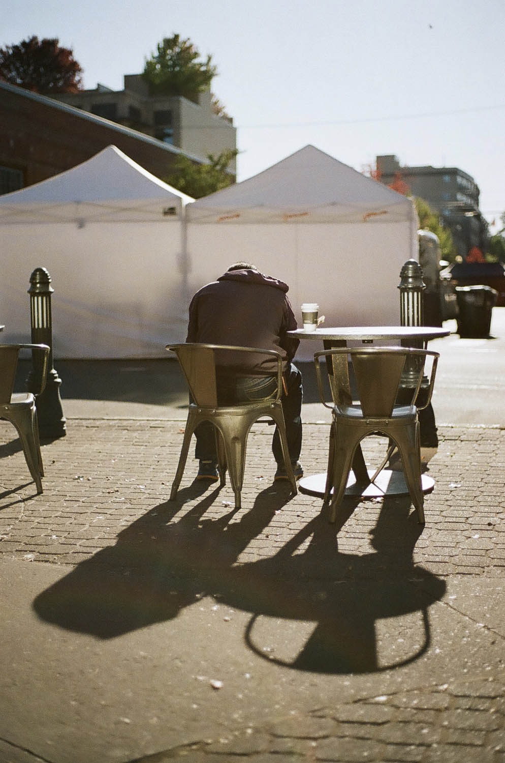 Lomography 400 ~ Canon AE-1 ~ Canon 50mm F1.8 Morning light bathes a man as he enjoys a coffee and a newspaper in downtown Bend, Oregon.