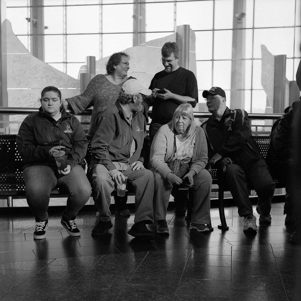A beam of light from the setting sun falls on people waiting at the airport in Anchorage, Alaska.